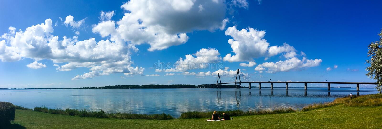 A loving couple having a summer picnic next to the water and the Faroe Bridges in southern Denmark. Farö, Denmark - July 15, 2017: A panorama showing the Far stock image