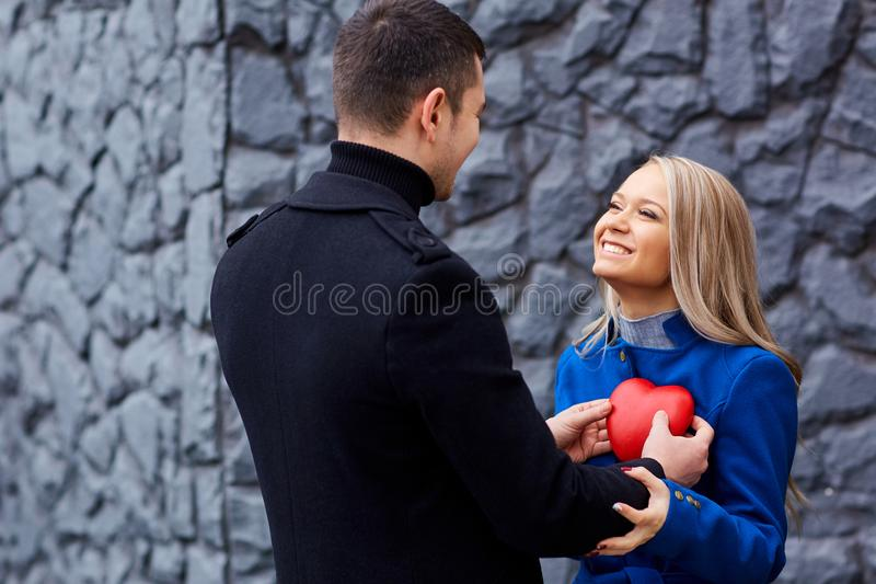 A loving couple with a heart on a gray background. royalty free stock images