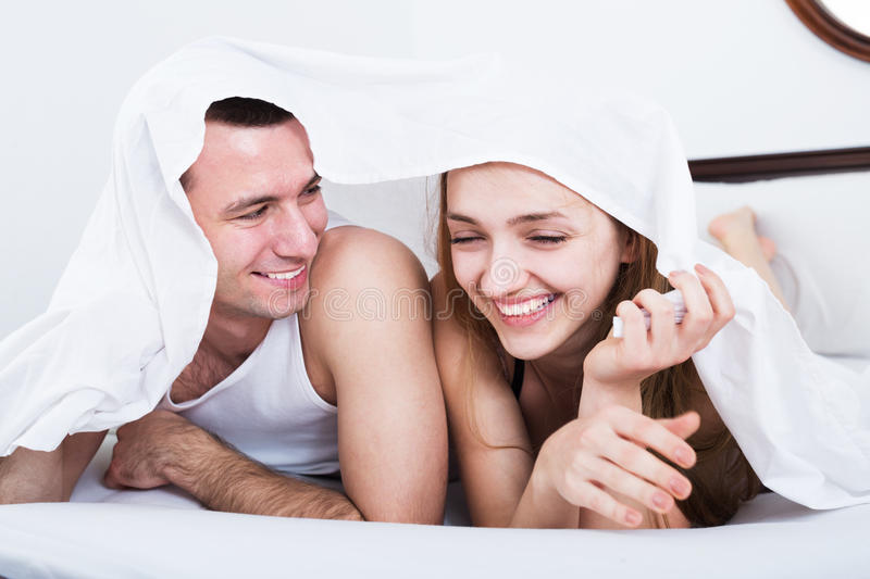 Loving couple hiding under cover stock images