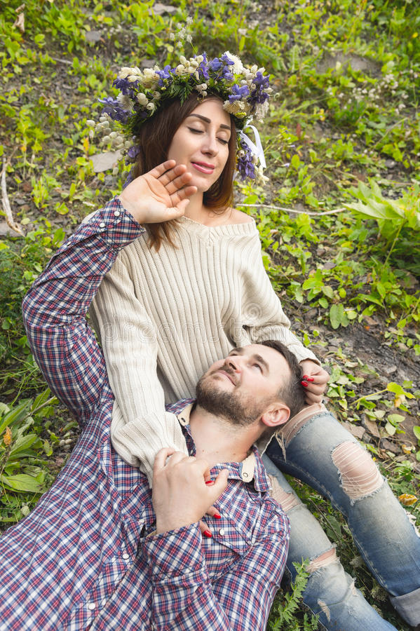 A loving couple of hipsters on walks. Hipster with a beard lies on the lap of his girl who wears a vinok of wildflowers. The concept of unity with nature and a royalty free stock photography