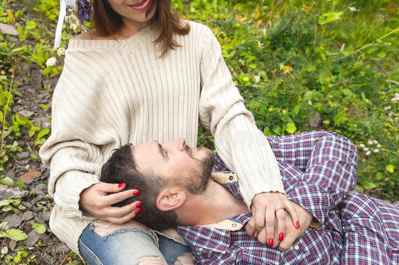 A loving couple of hipsters on walks. Hipster with a beard lies on the lap of his girl who wears a vinok of wildflowers. The concept of unity with nature and a stock image