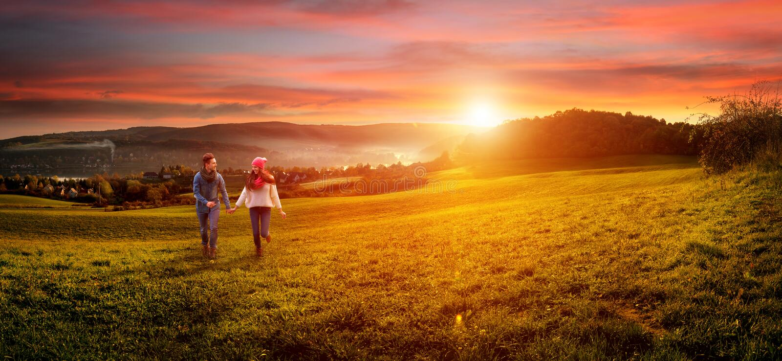 Loving couple holding hands running on the field.  stock image