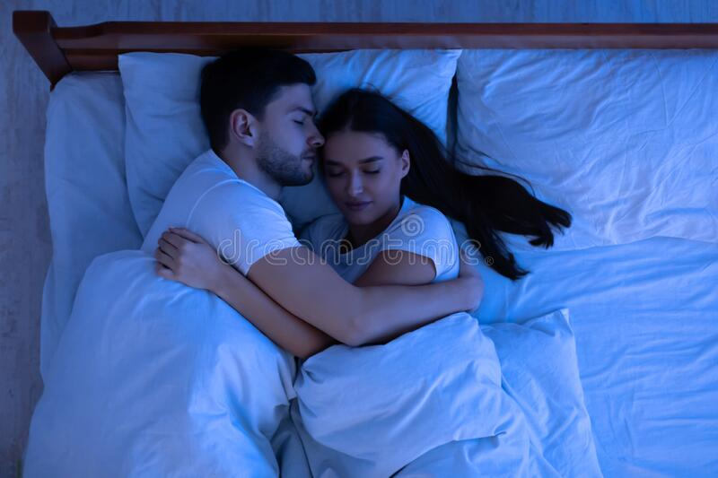 Loving Couple Hugging Sleeping In Bed At Home, Above View stock photo