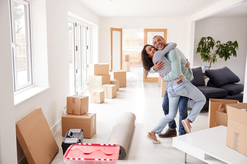 Loving Couple Hugging Surrounded By Boxes In New Home On Moving Day stock photos