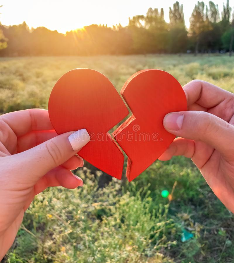 Loving couple joins together the halves of the heart. Concept of love and relationships. Reconciliation of a married couple. royalty free stock image