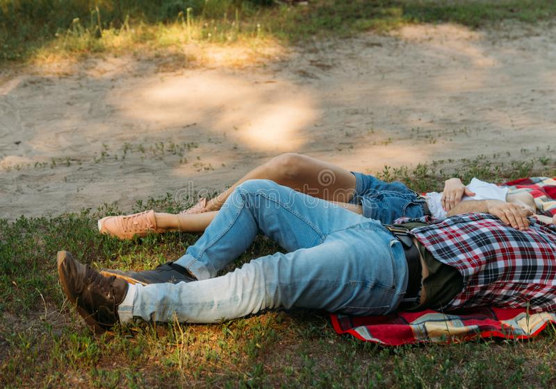 Loving couple lie, lie down on a red plaid in the woods and embrace.the couple is kissing. On the man dressed in a plaid shirt and jeans. a girl hugs a man stock photo