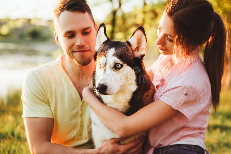 Lifestyle, happy family of two resting at a picnic in the park with a dog. royalty free stock images