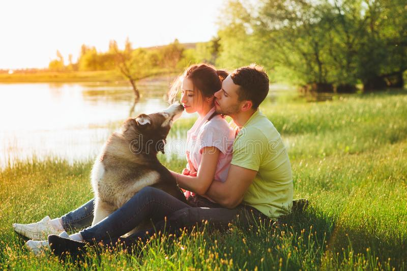 Lifestyle, happy family of two resting at a picnic in the park with a dog. stock photography