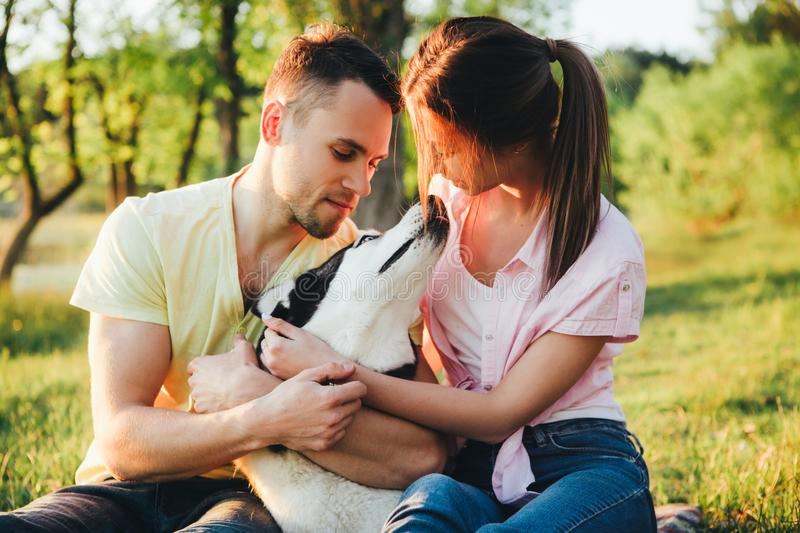 Lifestyle, happy family of two resting at a picnic in the park with a dog. stock images
