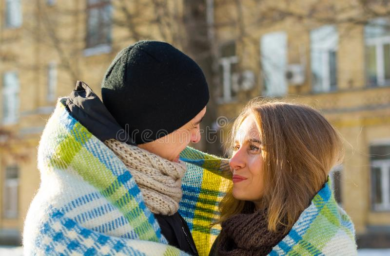 Loving couple looking at each other and laughing plaid in winter. The guy hugs a girl on the street in winter stock photo