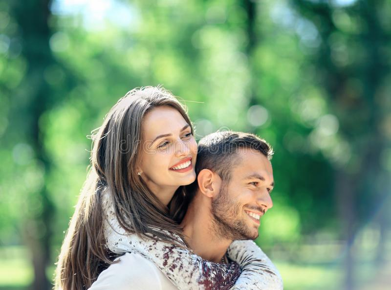 Loving couple man and woman having fun piggybacking in park. Loving couple men and women having fun piggybacking in park. Happy smiling boyfriend and girlfriend royalty free stock photo