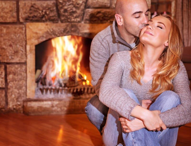 Loving couple near fireplace stock photo