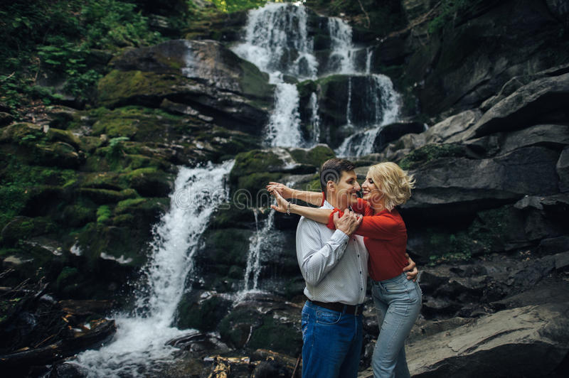 Loving couple near a waterfall in forest. royalty free stock photos