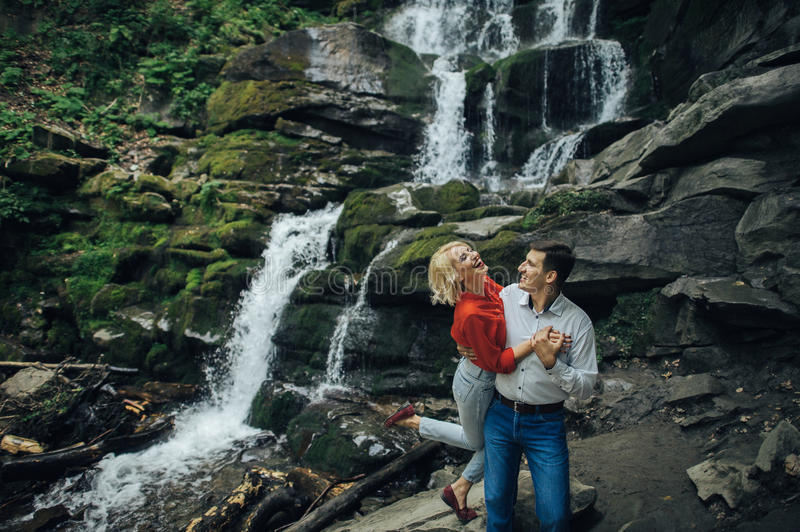 Loving couple near a waterfall in forest. royalty free stock photography