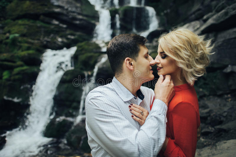 Loving couple near a waterfall in forest. stock photo