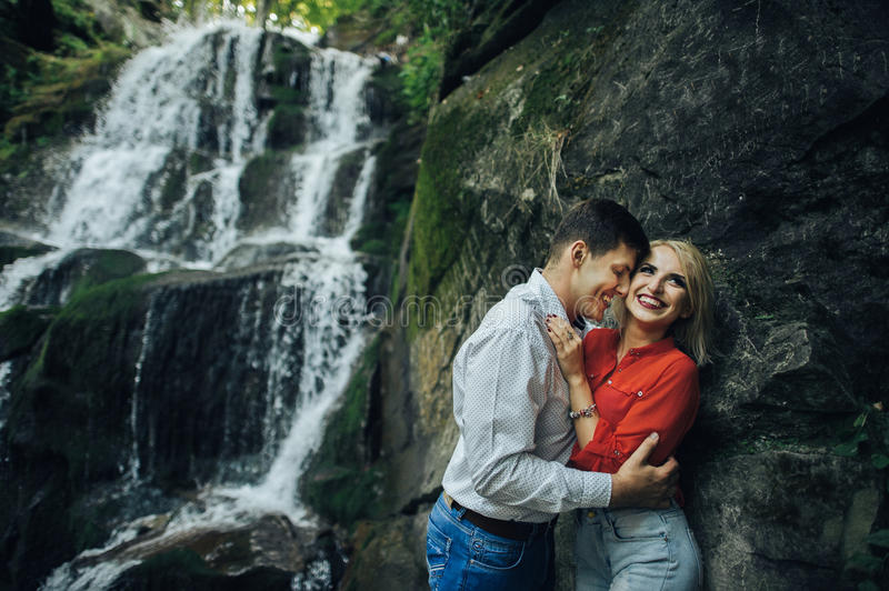 Loving couple near a waterfall in forest. stock photography