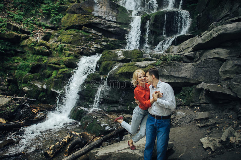 Loving couple near a waterfall in forest. stock image