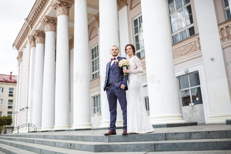 Loving couple of newlyweds walks in the city near columns royalty free stock photos