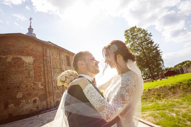 Loving couple of newlyweds walks near ancient old church in summer sunny day royalty free stock images