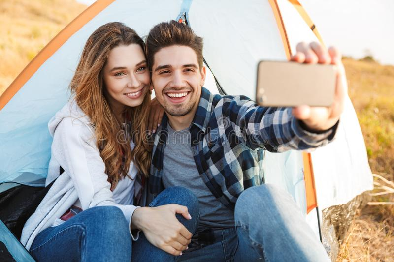 Loving couple outside in free alternative vacation camping take selfie by mobile phone. Photo of happy young loving couple outside in free alternative vacation stock photo