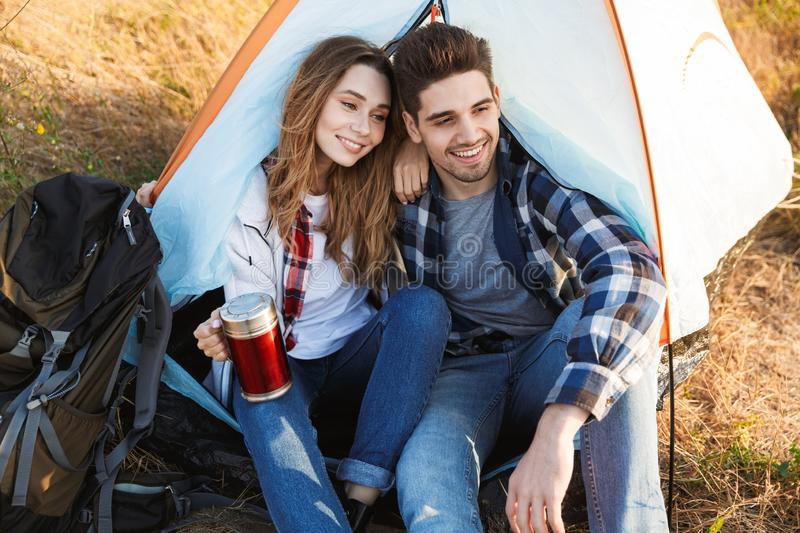 Loving couple outside in free alternative vacation. Photo of happy young loving couple outside in free alternative vacation camping drinking hot tea stock image