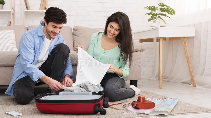 Loving couple packing clothes into suitcase at home. Prepare for trip. Loving couple packing clothes into suitcase, sitting on floor at home royalty free stock photo