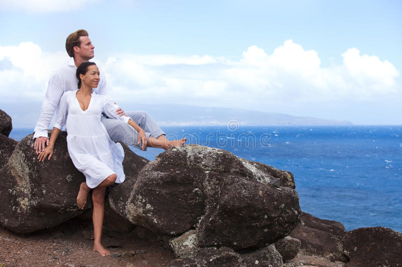 Loving couple in Paradise. Love on the rocks Newleyweds in Hawaii above the ocean on a Lava bluff stock photography