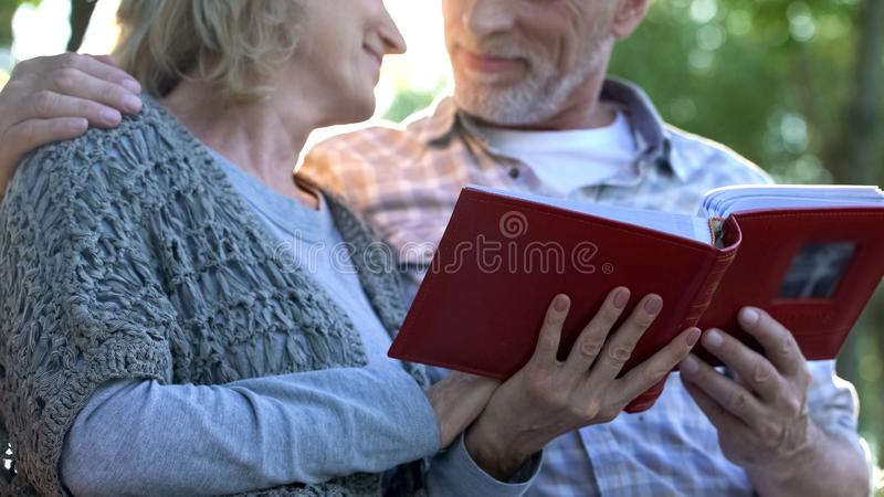 Loving couple with photobook tenderly looking at each other, pleasant moments stock photography