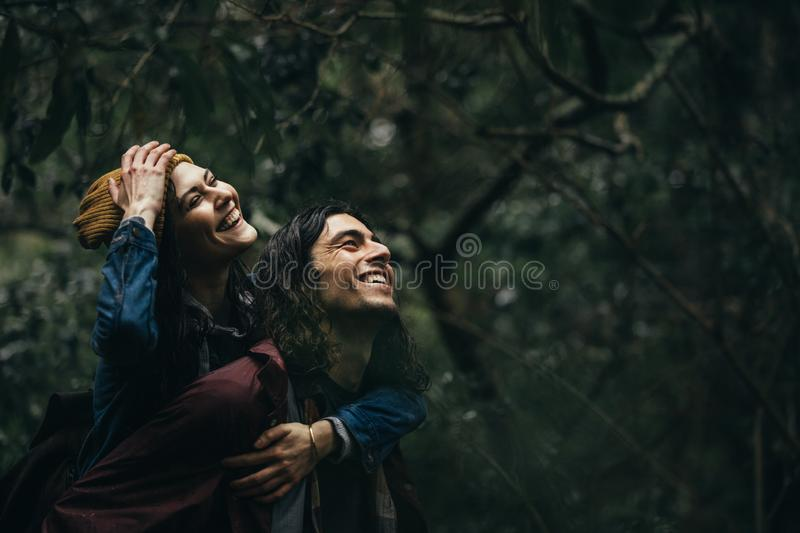 Loving couple piggybacking in the rain royalty free stock image