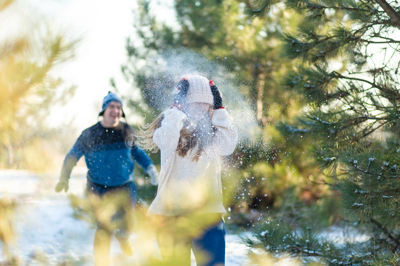 Loving couple play snowballs in winter in the forest. The guy sculpts and throws snowballs at the girl. Laugh and have a good time royalty free stock images