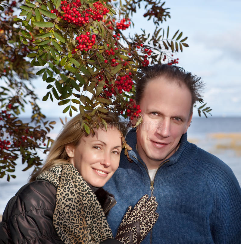 Loving couple .Portrait in a sunny day. Loving couple at a mountain ash bush royalty free stock image