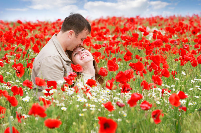 Loving couple on red poppies field royalty free stock images