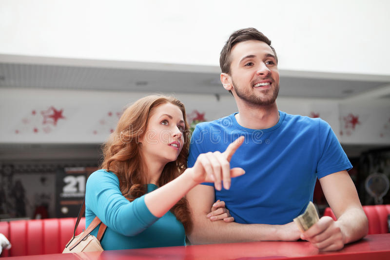 Loving couple at the restaurant. Young loving couple buying movie tickets royalty free stock photography