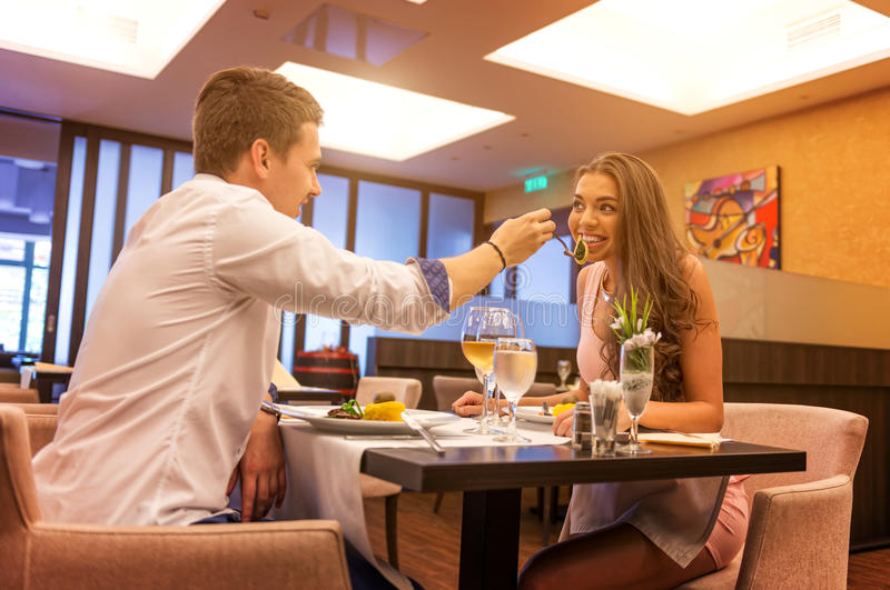 Loving couple restaurants, man feeds his love stock images