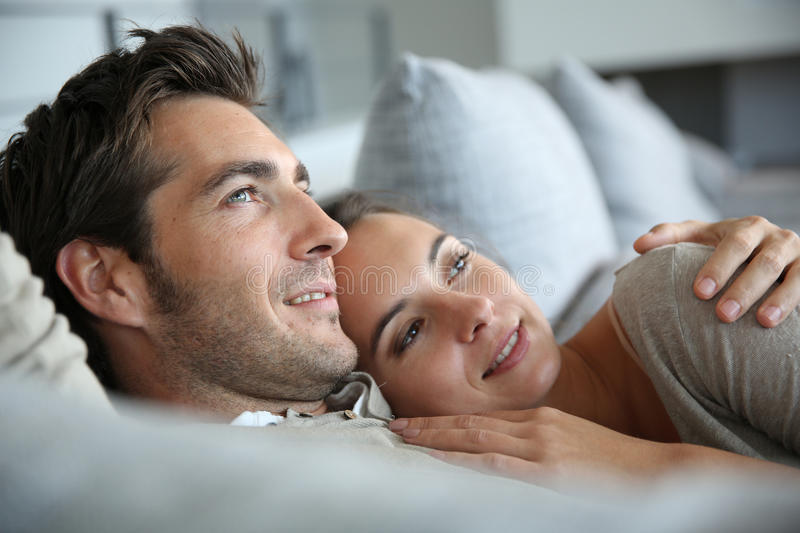 Loving couple resting in sofa royalty free stock photos