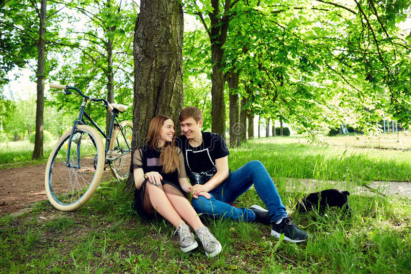 A loving couple is resting by tree on the grass in the park stock image