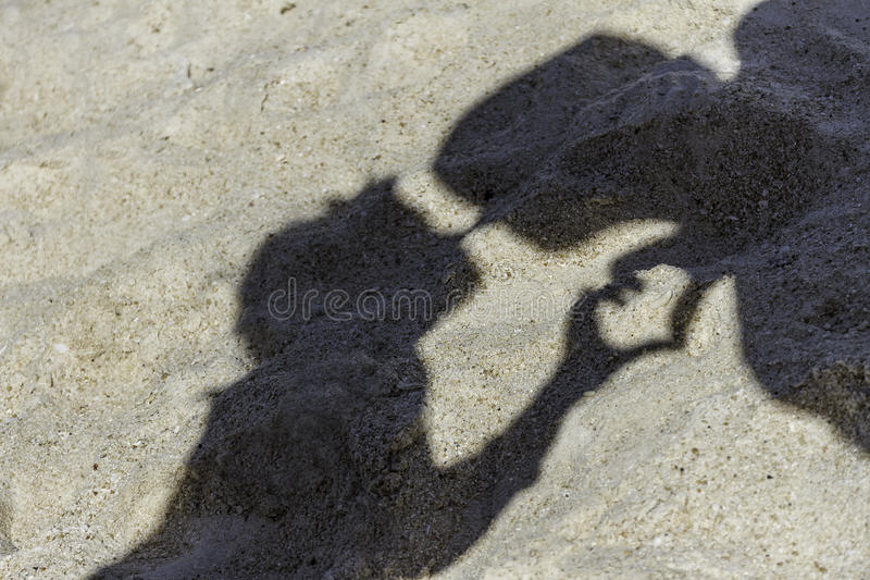 Loving couple shadows making a kiss on tropical sand beach stock images