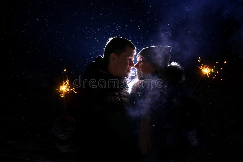 Loving couple silhouette. Back light and snow. royalty free stock images