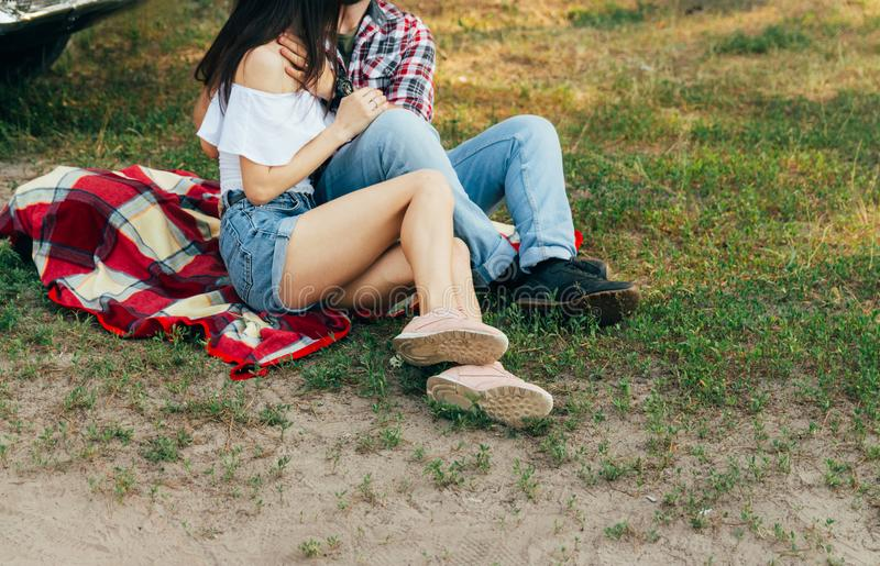 Loving couple sits on a red plaid in the woods and embrace.the couple is kissing. On the man`s arm is a black watch, dressed in a plaid shirt and jeans. a girl royalty free stock photo