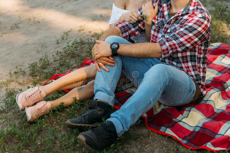 Loving couple sits on a red plaid in the woods and embrace.the couple is kissing. On the man`s arm is a black watch, dressed in a plaid shirt and jeans. a girl stock images