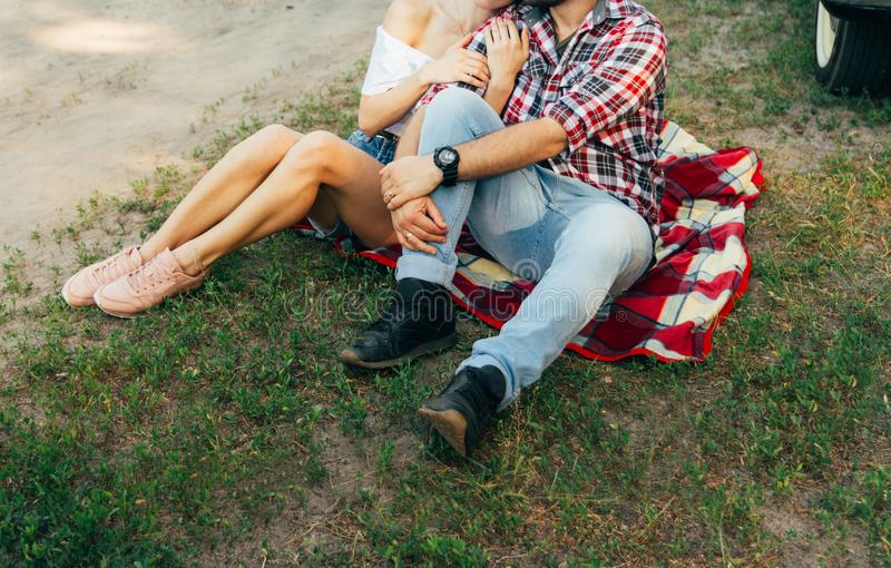 Loving couple sits on a red plaid in the woods and embrace.the couple is kissing. On the man`s arm is a black watch, dressed in a plaid shirt and jeans. a girl stock photography