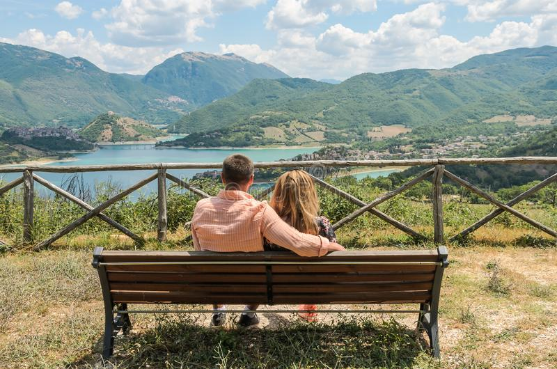 Loving couple sitting on a bench against the backdrop of a mountain lake Lago del Turano - happy family stock photos