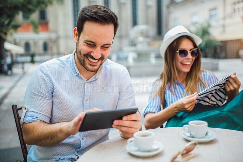 Loving couple sitting in a cafe enjoying in coffee and conversation after shopping stock photography