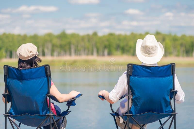 A loving couple sitting on chairs near a beautiful lake stock image