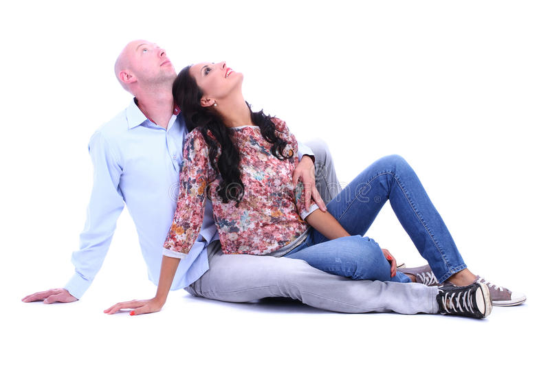 Loving couple sitting on floor and looking up on white stock photo