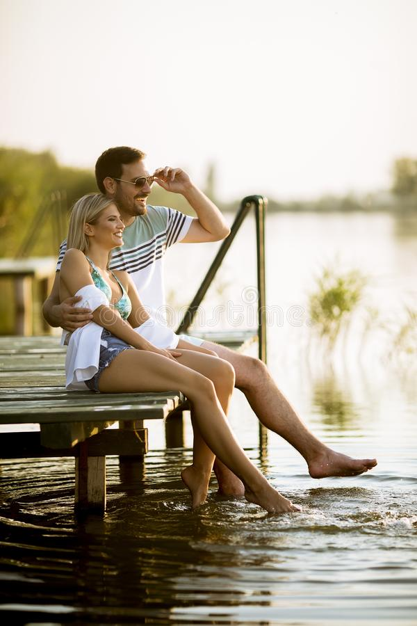 Loving couple sitting on the pier on lake stock photos