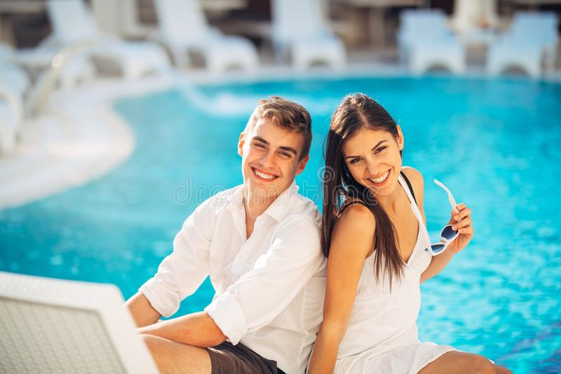 Loving couple spending vacation on tropical resort swimming pool.Newlyweds honeymoon on seaside. Couple in true love.Flirting and showing emotions.Affection stock photos