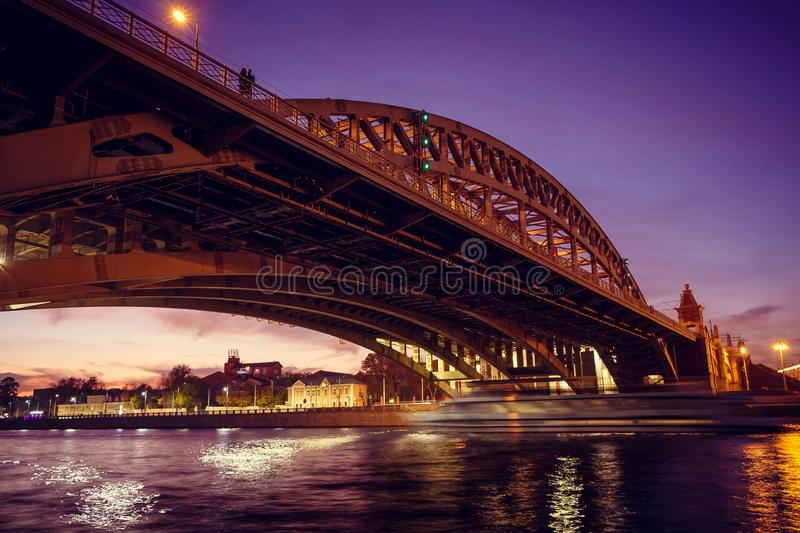 A loving couple is standing on a bridge over the river of the evening city. In the distance stock photography