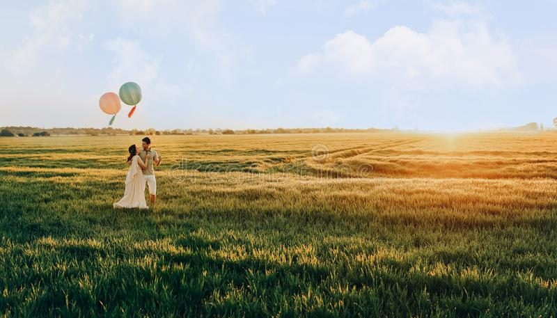 Loving couple standing in the field with helium colored balls stock image