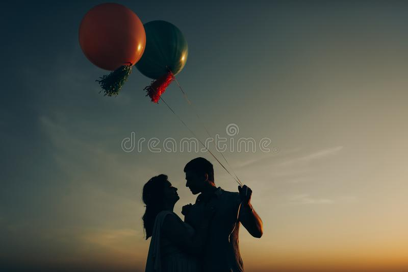 Loving couple standing in the field with helium colored balls stock photo